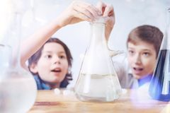 Close up of schoolboys during chemistry practical session. Wow magic is real. Amazed little scientists standing with slack jaws while looking at a result of a Royalty Free Stock Photo