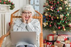 Charming senior lady is working on computer in holiday Royalty Free Stock Photo