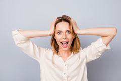 Wow! It`s unbelievable! Shocked happy woman with opened mouth to. Uching her head isolated on gray background royalty free stock image