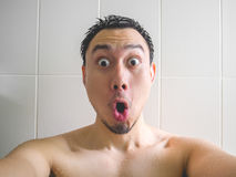 Wow and shocked face man taking selfie in bathroom. Stock Images