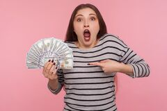 Free Wow, So Much Money! Portrait Of Shocked Young Woman In Striped Sweatshirt Screaming In Amazement And Pointing Dollar Bills Royalty Free Stock Image - 185191156