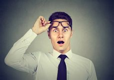 Wow! Surprised handsome man with opened mouth taking off glasses. Wow! Surprised young handsome man with opened mouth taking off glasses royalty free stock image