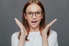 Wow, thats great! Surprised pleased beautiful woman has pleasant appearance, spreads palms near face, opens mouth from wonder,. Dressed in casual t shirt royalty free stock photos