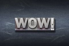 Wow exclamation den. Wow word made from metallic letterpress on dark jeans background royalty free stock images