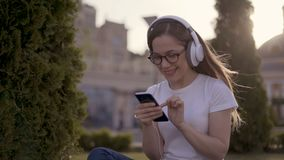 Wow! Young surprised girl student in a large white headphone sits in a park and typing a message on the telephone. 4K stock footage