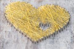 Сердце сделанное ногтей на древесине с wowen строка золота Стоковое фото RF