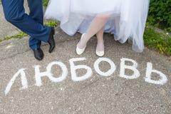 Wpisowa miłość w rosjaninie na drodze nogi państwo młodzi fotografia royalty free
