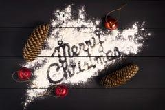 Wpisowi Wesoło boże narodzenia, pisać z mąką na ciemnym drewnianym tle karciany bożego narodzenia powitanie obraz royalty free