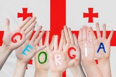 Wpisowy Gruzja na dziecko rękach przeciw tłu falowanie flaga Gruzja zdjęcia stock