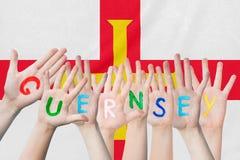 Wpisowy Guernsey na dziecko rękach przeciw tłu falowanie flaga Guernsey obrazy royalty free