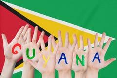 Wpisowy Guyana na dziecko rękach przeciw tłu falowanie flaga Guyana zdjęcie royalty free