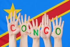 Wpisowy Kongo na dziecko rękach przeciw tłu falowanie flaga Kongo obraz royalty free