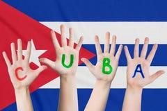 Wpisowy Kuba na dziecko rękach przeciw tłu falowanie flaga Kuba fotografia royalty free