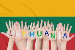 Wpisowy Lithuania na dziecko rękach przeciw tłu falowanie flaga Lithuania obraz stock