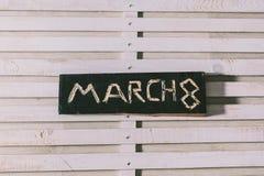 Wpisowy Marzec 8 ciie out na czarnej drewnianej desce obrazy stock