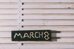 Wpisowy ` Marzec 8 ` ciie out na czarnej drewnianej desce folwarczki obrazy royalty free