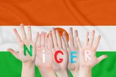 Wpisowy Niger na dziecko rękach przeciw tłu falowanie flaga Niger zdjęcia stock