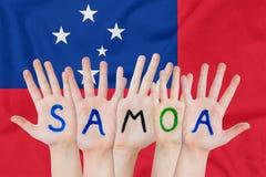 Wpisowy Samoa na dziecko rękach przeciw tłu falowanie flaga Samoa obraz stock