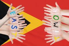 Wpisowy Timor Wschodni na dziecko rękach przeciw tłu falowanie flaga Timor Wschodni zdjęcia stock