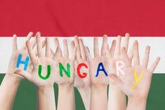 Wpisowy Węgry na dziecko rękach przeciw tłu falowanie flaga Węgry obraz royalty free