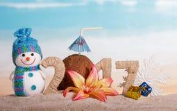 Wpisowy 2017 w piasku, bałwan, Bożenarodzeniowa piłka na tle ocean Zdjęcie Royalty Free