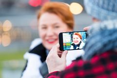 wpman的图片在智能手机的在街道上 妇女画象多孔电话照相机的 关闭智能手机 库存照片