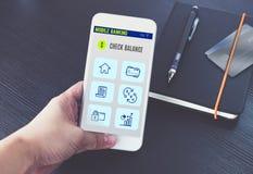 Wręcza mieniu mobilnego bankowości app na ekranie z czarnym notatnikiem i kartę kredytową na czarnym drewnianym biurku, Cyfrowych obrazy stock