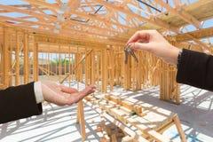 Wręczać Nad kluczami Na miejsca Inside Nowej Domowej budowie Frami Zdjęcia Stock