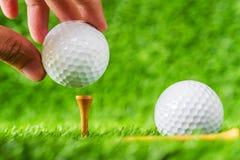 Wręcza chwyt piłkę golfową stawiającą na trójnika brązu drewnie z zielonej trawy backg obraz royalty free