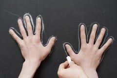 Wręcza chwyta kawałek kreda i rysuje obwód inna ręka f zdjęcie stock