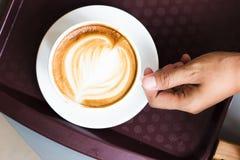 Wręcza chwytowi kawowego latte w białej filiżance od odgórnego widoku zdjęcie royalty free