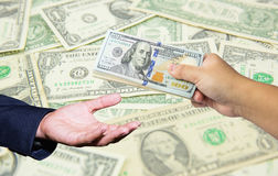 Wręcza chwytowi wiele dolara amerykańskiego z dolara amerykańskiego banknotu tłem Zdjęcia Royalty Free