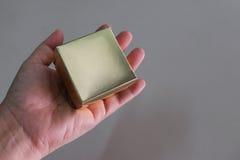 Wręcza chwytowi złocistego kwadratowego pudełko na prostym tle Obrazy Stock