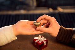 Wręcza czekać serce i obsługuje rękę trzyma złotego serce Zdjęcia Stock