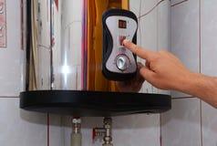 Wręcza dorosłych mężczyzna obraca daleko woda w elektrycznym bojlerze Zakończenie samiec up wręcza obracać dalej guzika elektrycz Zdjęcia Stock