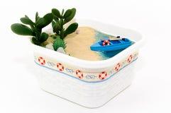 Wręcza gosposi, miniaturyzuje plażę z łodzią na piaskowatym brzeg, Błękitne wody z skorupami i roślinami fotografia royalty free