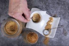 Wręcza kładzenia brązu cukier w białym porcelany filiżanka kawy obraz royalty free