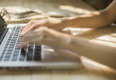 Wręcza kobiety pisać na maszynie na laptopie na drewnianym biurku Zdjęcie Royalty Free
