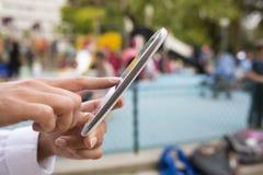 Wręcza kobiety używa jej telefonu komórkowego tła boisko obrazy royalty free