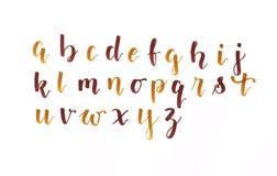 Wręcza literowanie, nowożytnego kaligrafii abecadło w jesiennym koloru brązie i złoto na białym papierze, ręcznie pisany ilustracji