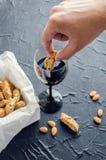 Wręcza maczaniu Włoskich cantuccini ciastka w czerwone wino Obrazy Stock