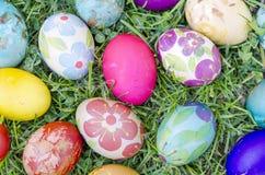 Wręcza malującemu decoupage Wielkanocnych jajka na trawie Obraz Royalty Free