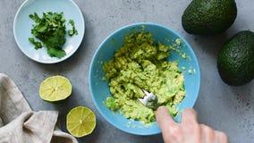 Wręcza mashing avocado w pucharze zdjęcie wideo