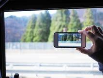 Wręcza mienia smartphone brać wideo na autobusowym chodzeniu zdjęcia stock