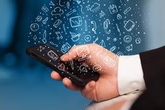 Wręcza mienia smartphone z ręka rysującymi medialnymi symbolami i ikonami Zdjęcie Royalty Free