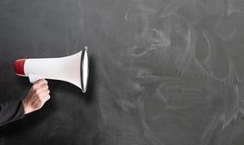 Wr?cza mienie bielu i czerwieni megafon przeciw chalkboard zdjęcia royalty free