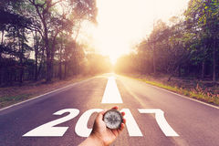 Wręcza mienie kompas na Opróżniałam asfaltowej drodze i nowego roku 2017 pojęciu Obrazy Stock