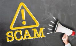 Wręcza mienie megafon przeciw chalkboard z słowem SCAM i znakiem ostrzegawczym obraz royalty free