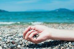 Wręcza mienie otoczaki na plaży, turkusowa woda morska w plecy Obrazy Royalty Free