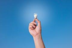 Wręcza mienie PROWADZĄCĄ żarówkę z oświetleniem na niebieskiego nieba tle Zdjęcia Royalty Free